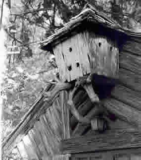 photo of bird house attached to top front of cabin designed to match the log cabin