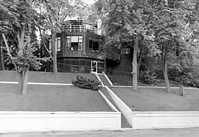 three story house on a small wooded hill with stairs going up to it