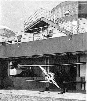 backside of a three story house with a airplane garage as part of the first floor