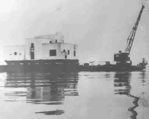 photo from 1935 of house on a barge with a crane in lake michigan