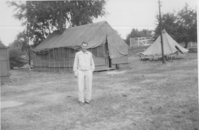 old black & white photo of camp director standing in front of tents