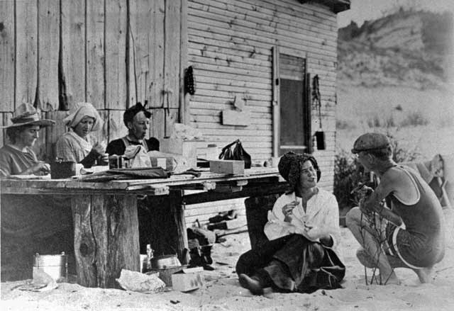 Prarie club members sitting outside of a cabin.