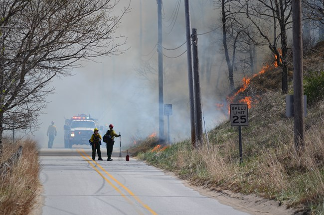 Firefighters and fire engine on the road during prescribed fire.