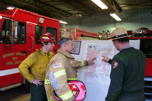Firefighters in front of  map discussing tactics on a wildfire