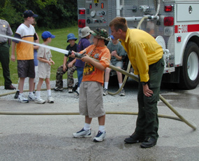 Firefighter and a child spraying water out of fire hose