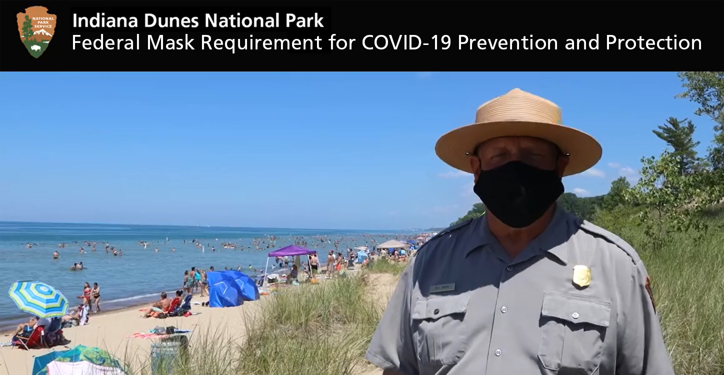 Photo of ranger with mask on at beach.