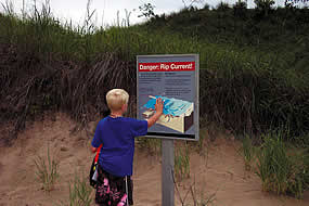 boy standing in front of a sign during the summer that talks about rip currents