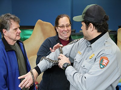 Ranger shows a milk snake to a couple of visitors.