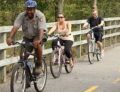 Ranger riding a bicycle with visitors along a paved bike trail.