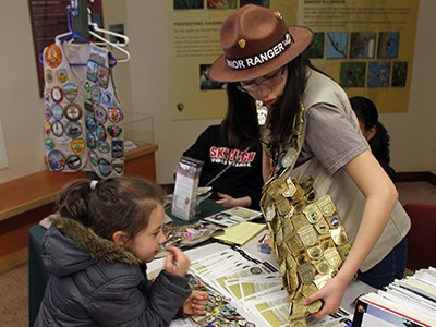 Volunteer with vest full of Junior Ranger badges helps young girl learn about the Junior Ranger program.
