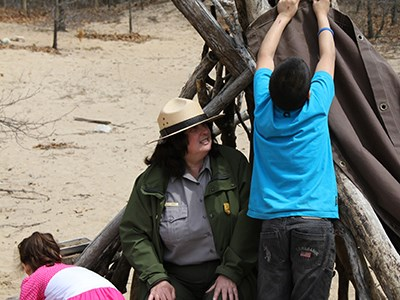 Ranger helps children build a fort out of driftwood and tree branches.