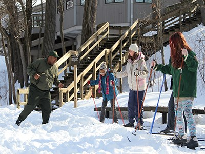 Ranger teaches children how to move on cross-country skis.