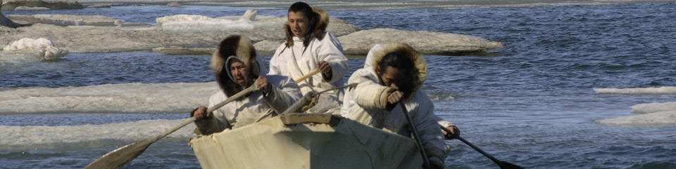 Three Iñupiat men paddling a whaling boat