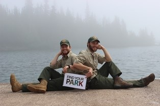 Two visitor services volunteers pose on the ground in front of Lake Superior for a photograph with a Find Your Park sign.
