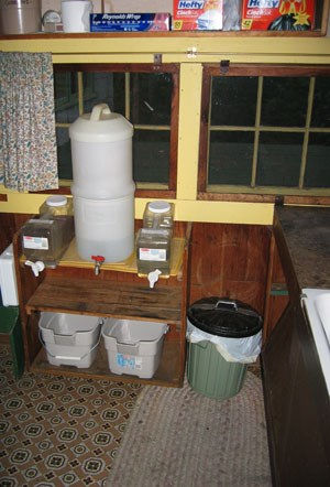 A drip water filtration system in the small kitchen of a cabin