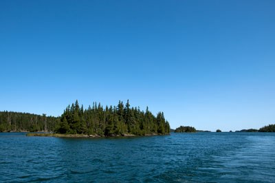 A scenic view of Tobin Harbor taken from a boat, blue sky, small island, blue water.
