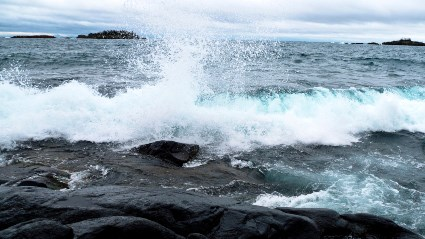 A photograph shows a wave rolling onto a rocky shoreline with an overcast sky