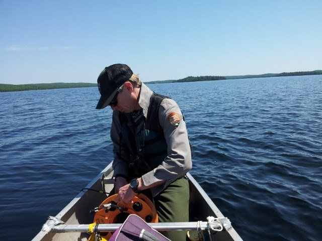 A biologist lowers an instrument in a lake from a canoe to take scientific measurements