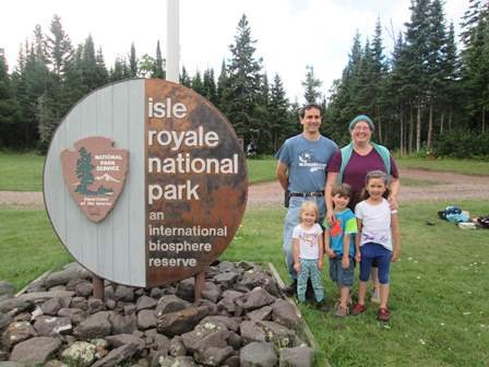 A family stands for a photo around the Isle Royale International Biosphere Sign