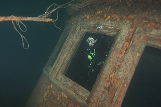 A diver inside the pilot house of the Chester Congdon.