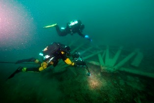 Divers swim over wreckage from the shipwreck, Cumberland