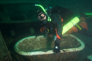 Diver poses with bathtub from the shipwreck, Monarch.