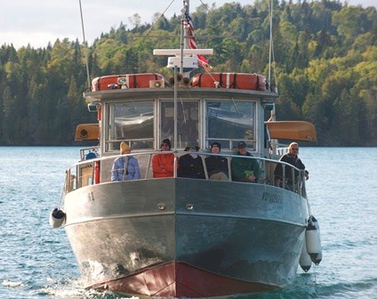 The Voyageur II passenger vessel as seen from the bow sailing for Isle Royale. Passengers sit along the bow cabin windows.