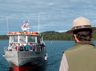 A ranger greets visitors arriving on the Voyageur II ferry.