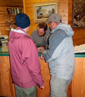 Visitors stand in front of a visitor desk, obtaining a camping permit from a park ranger.