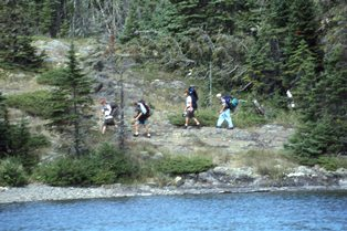 A group of backpackers hike the Rock Harbor Trail along Rock Harbor Channel