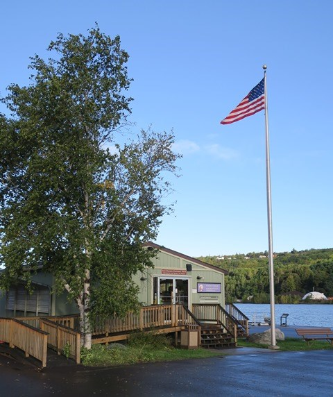 Houghton Visitor Center front entrance with handicap accessible ramp and American flag flying.