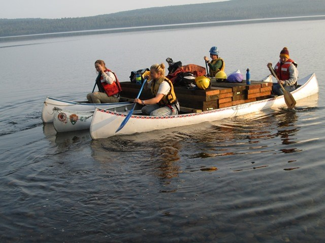 Trail Crew transports boards across Siskiwit Lake strapped to canoes.
