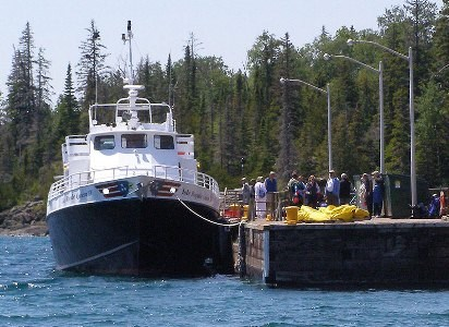 Isle Royale Queen IV moored at the Rock Harbor dock. Passengers line the dock. Boreal forest in the distance.