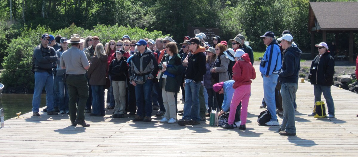Visitors attend a ranger program at the Windigo dock