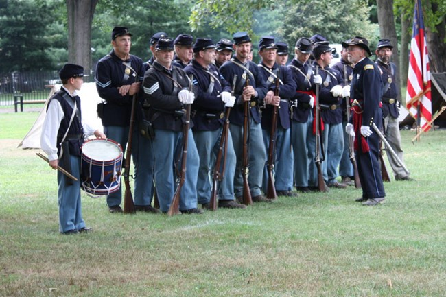 Picture of Civil War reenactors standing at attention waiting for orders from their commander.