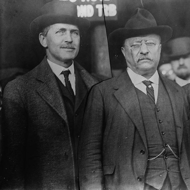 two men in suits standing side by side