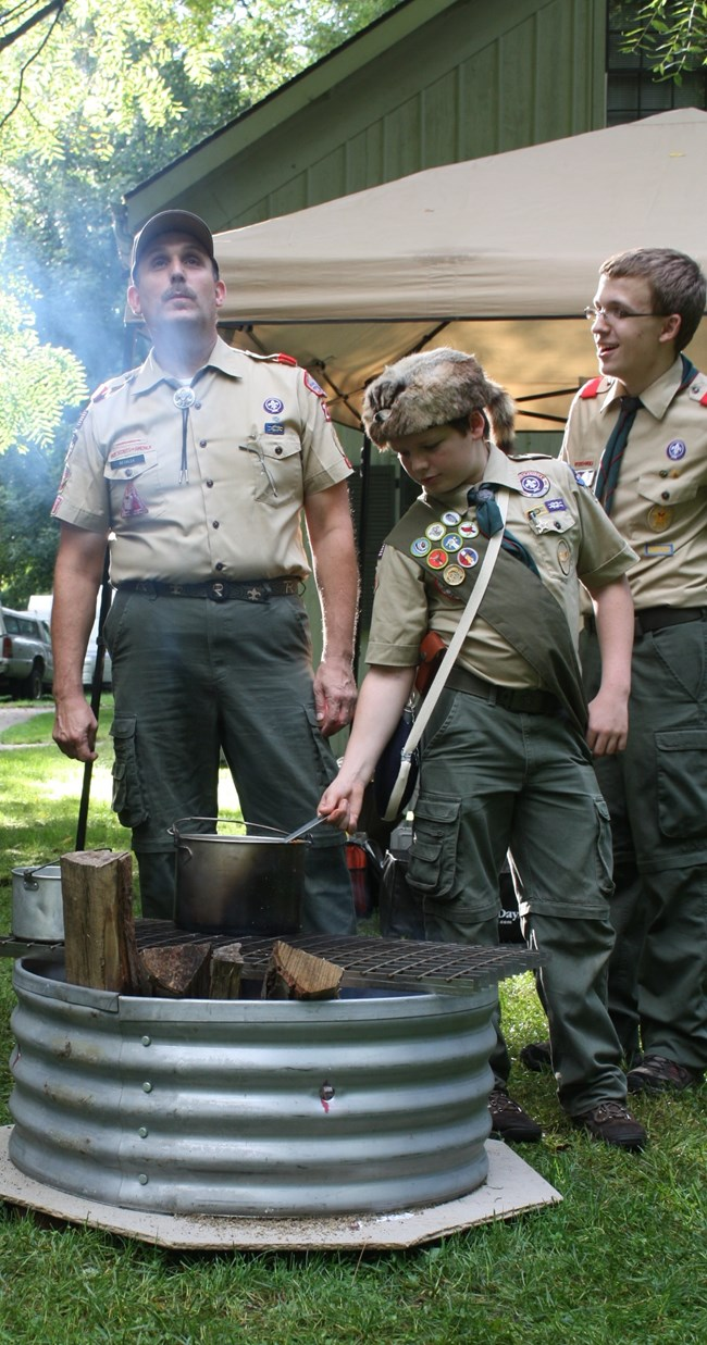 Boy scouts cooking food over a fire