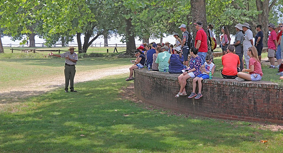 A park ranger talks to a group of visitors. The group sits along a curved brick wall in a grove of trees.