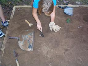 Child using a trowel to dig for artifacts