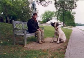 Visitor with dog on a leash resting along the Jamestown Seawall