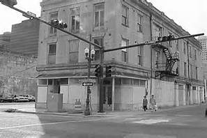 Black & white image of a three story brick building at the intersection of two streets.