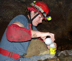 A physical science intern takes a water sample inside the cave