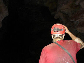A cave explorer looks into a large, dark passage