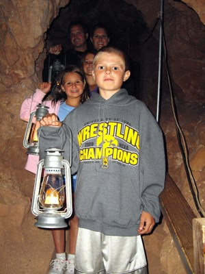 A family enjoys the Historic Lantern Tour route in Jewel Cave.  This tour is offered only during the summer months.