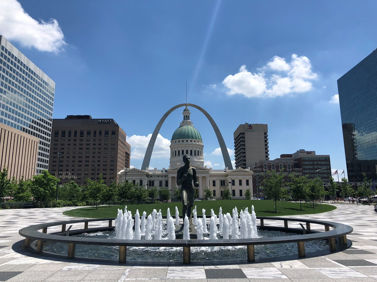 The Gateway Arch and Old Courthouse as seen from Kiener Plaza behind a fountain and statue of a man running