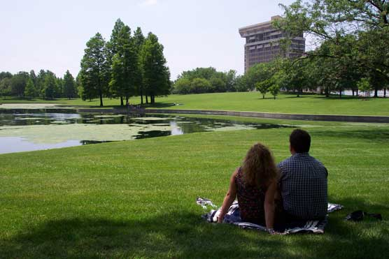 Couple with backs to camera sitting by the lagoon.