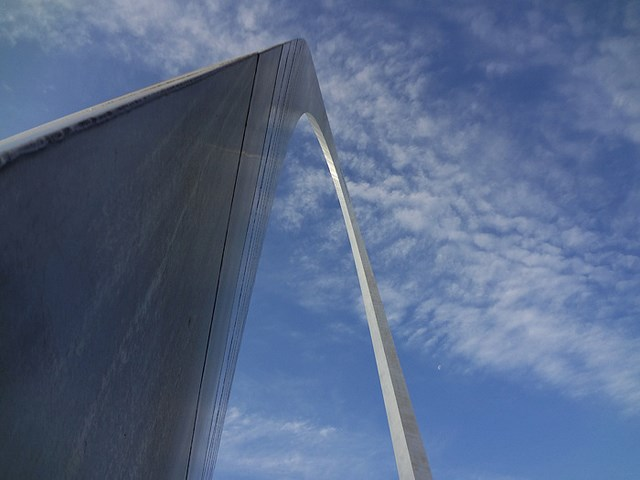 Looking up at the curve of the Gateway Arch against a blue sky