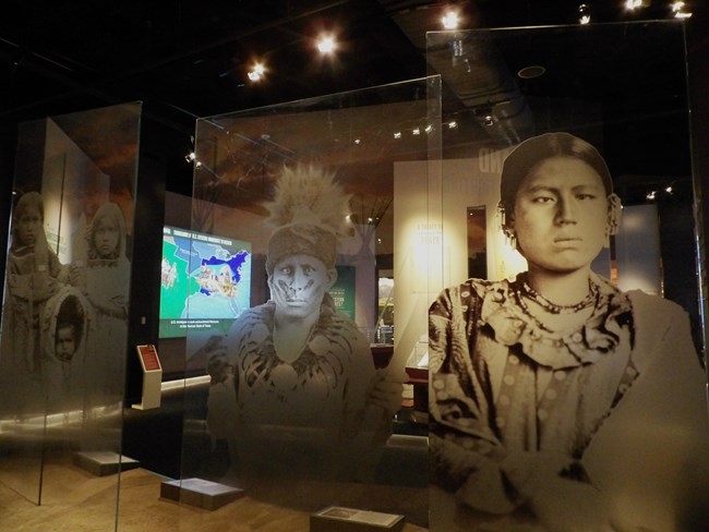 large images of American Indian woman and man with computer interactive visible behind