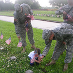 Men in uniforms and a little boy put flags on national cemetery graves