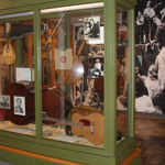 Image of exhibit case filled with photos and music instruments